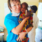 London dentist Monika holding a baby in Tanzania