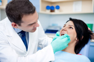 Dental implant specialist performing dental procedure on young woman