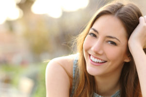 Woman in park smiling with beautiful smile