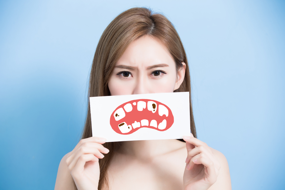 Woman holding an image of tooth decay over her mouth