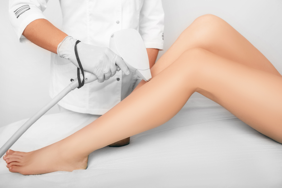 professional using laser hair removal tool on a patients legs